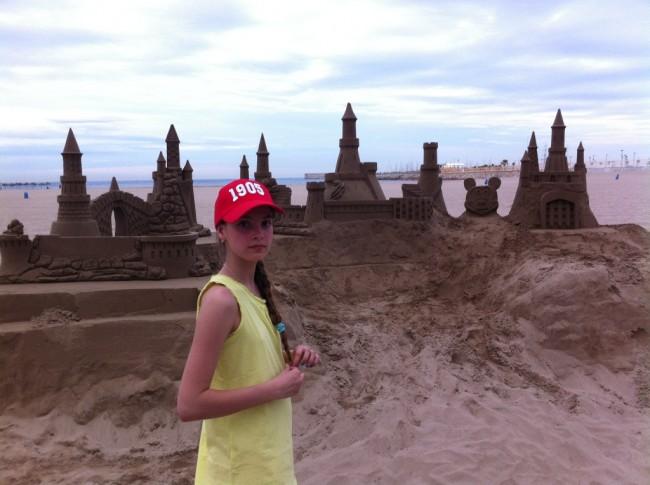 В новой кепке, на переполненном пляже Валенсии, доча играет в пасочки.