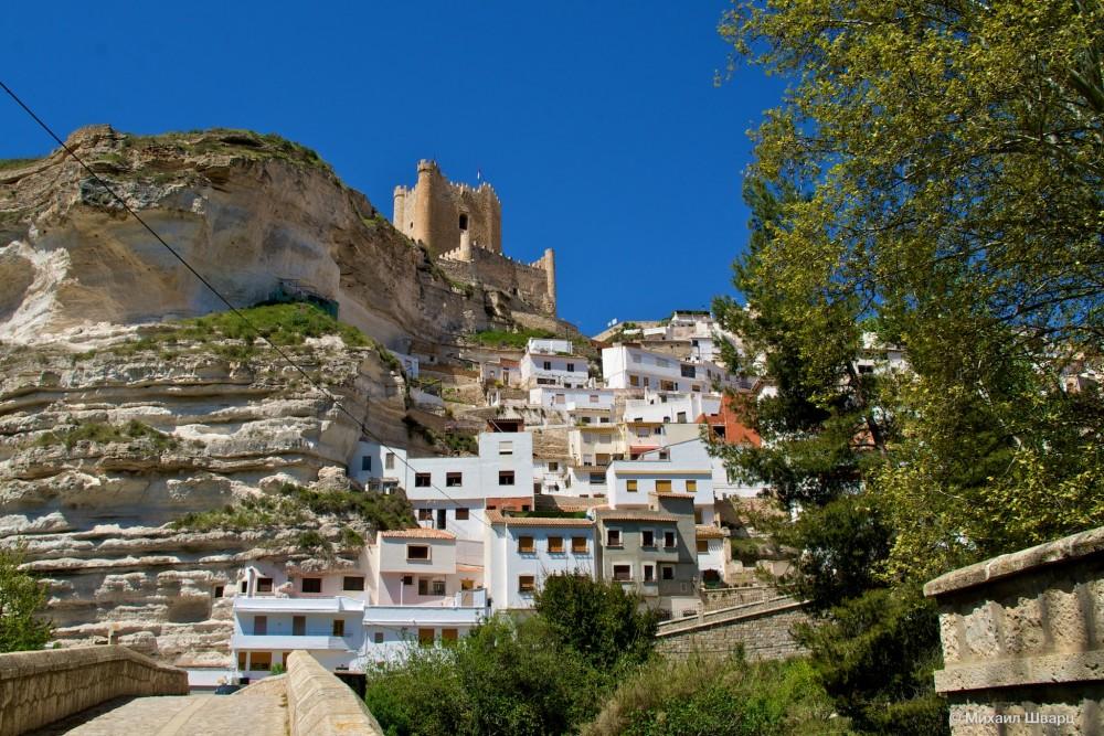 Замок над белыми домами, комнаты которых, буквально вырублены в скале